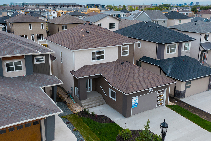 16. 283 John Neufeld - Aerial Front Elevation Broadview Homes The Avalon DG 15 A with acrylic stucco in a cool brown, overhead garage door with glass inserts and covered concrete front entrance