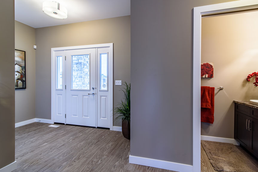 Contemporary style front foyer entrance with Vinyl Plank flooring, white MDF baseboards and casing and front door with double sidelites, in brown tones