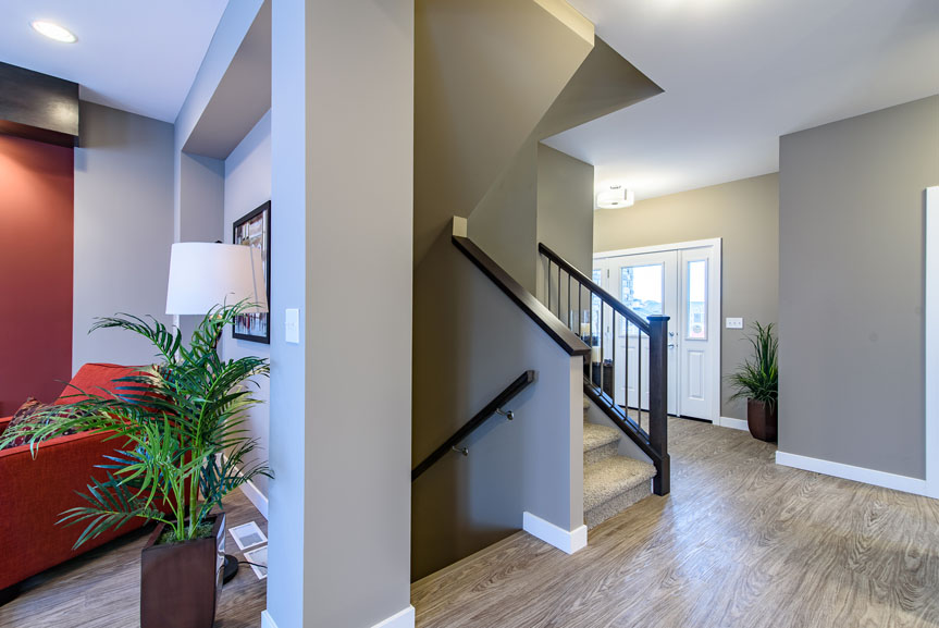 Contemporary front entrance with vinyl plank flooring, mdf baseboards and casing, and maple handrail at stairs with wrought iron spindles