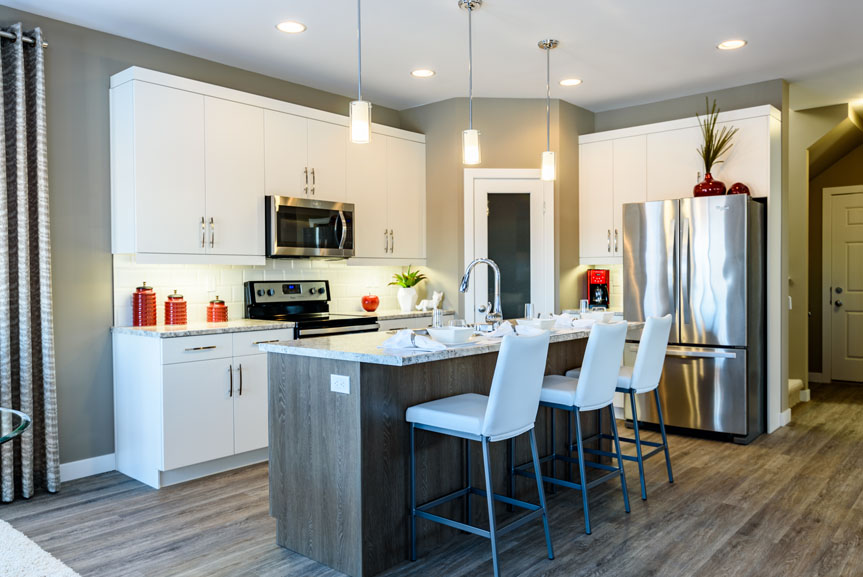 Contemporary Kitchen with Soho Satin White Cabinets, Island in Soho Woodgrain Flint, Vinyl Plank Flooring in Zodiac, Elite Kitchen Counter Top and Stainless Steel Appliances
