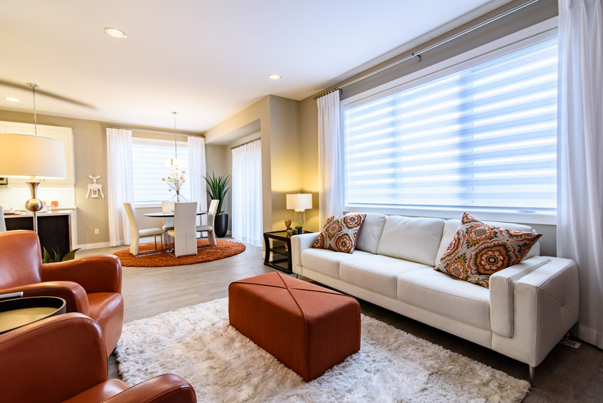 Contemporary Great Room with Torly's Laminate Flooring, Beige Walls, White Couch and Burnt Orange Accent Chairs