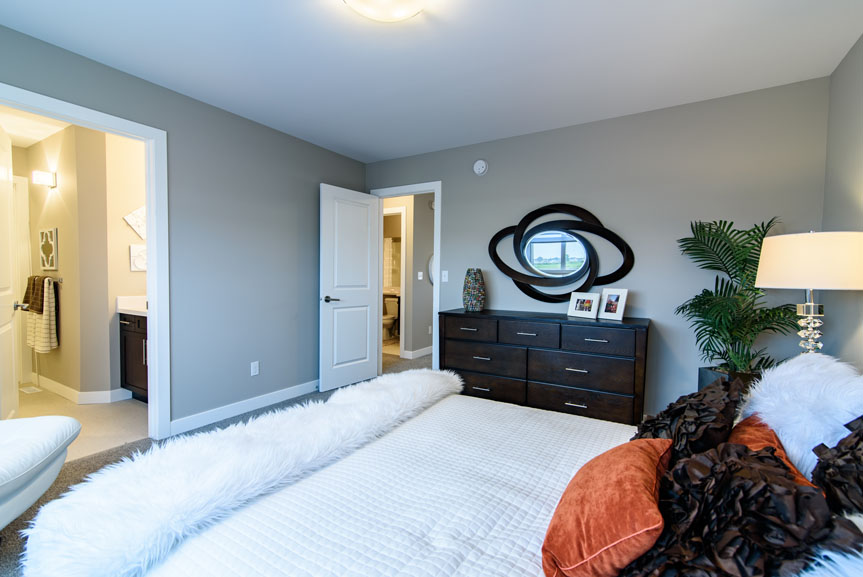 Contemporary Master Bedroom with Beige Walls and Orange Accents