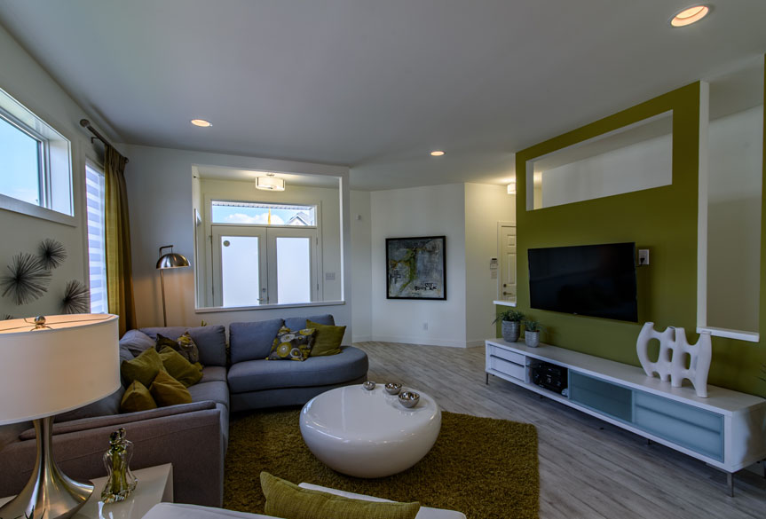 Open Concept Great Room with Laminate Flooring and Green Accent Wall