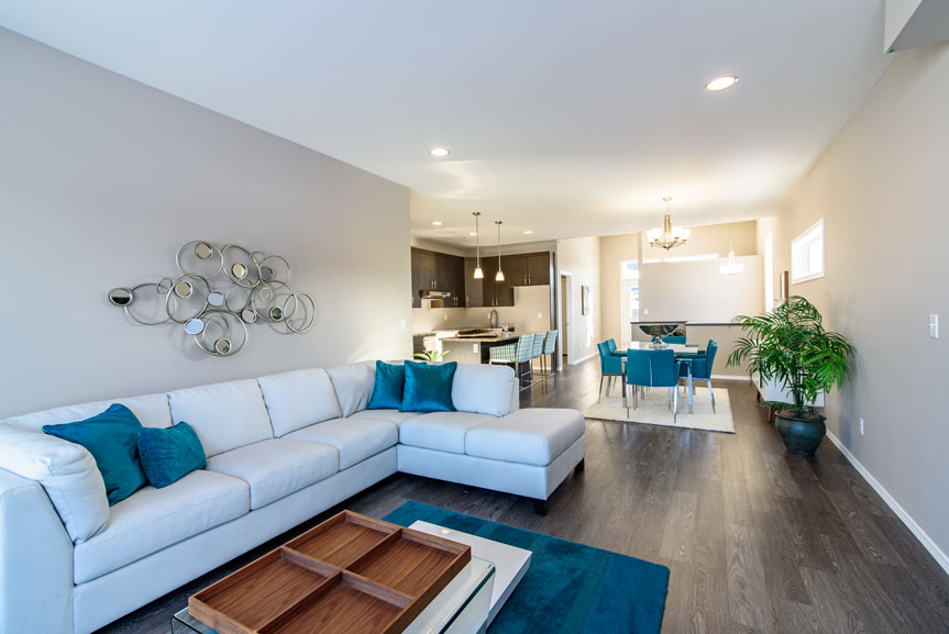 Open Concept Great Room with Armstrong Vivero Charlestown Oak Vinyl flooring, beige walls and teal accents