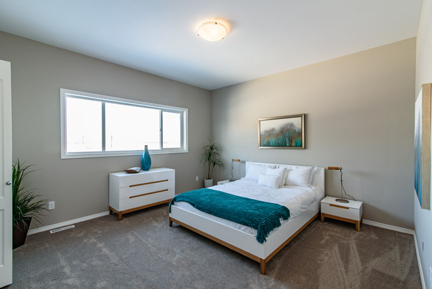 "Large Master Bedroom with walk-in closet and attached Ensuite, Dawson Manor carpet, stainmaster pad and beige walls with teal accents, and large 96"" x 40"" slider window"