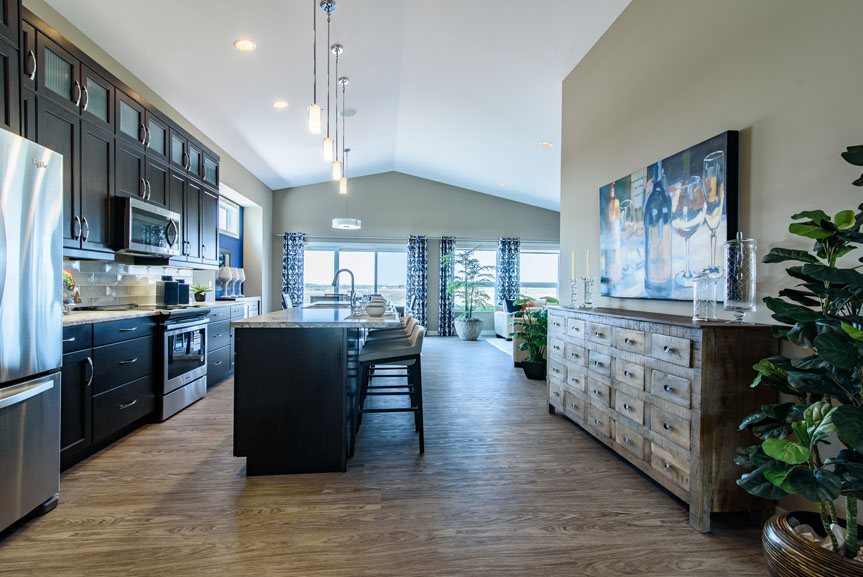 Open concept Kitchen with vinyl plank flooring, tamarind maple cabinets, large island and stainless steel appliances