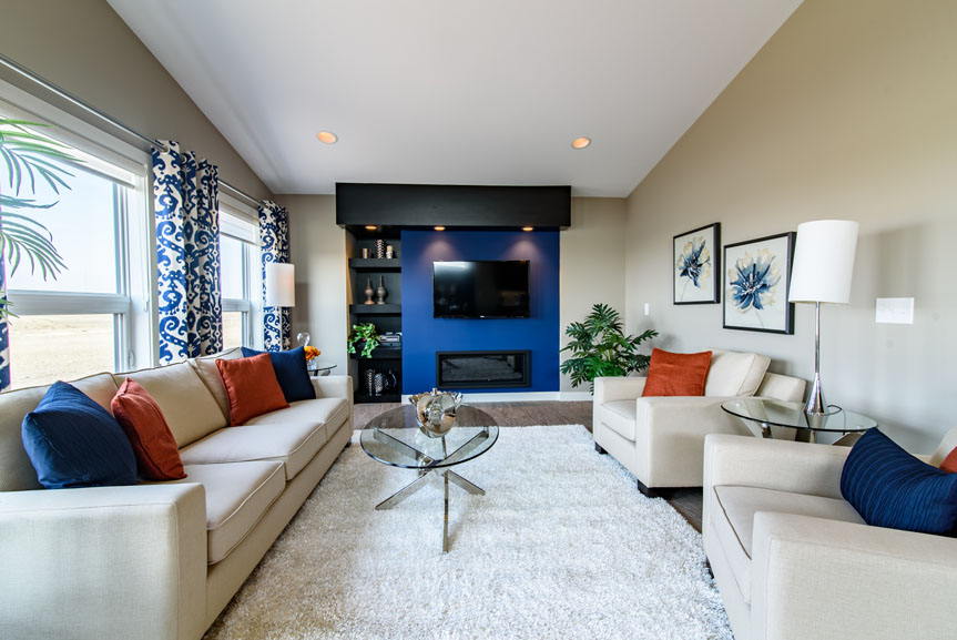 open concept great room with vinyl plank flooring, beige walls, blue accent wall and orange and blue accent decor