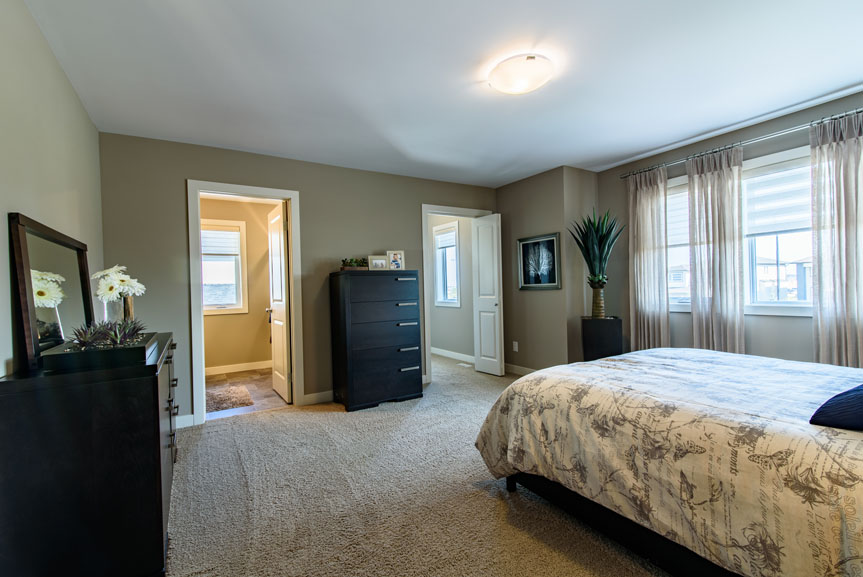 large master bedroom with beige carpet and walls