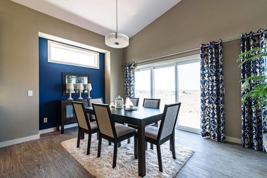 open concept dining room with vinyl plank flooring, beige walls, blue accent wall and dark wood furniture