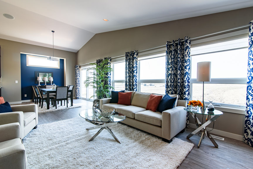 open concept great room and eating area with vinyl plank flooring, blue accent wall and blue and orange accent decor