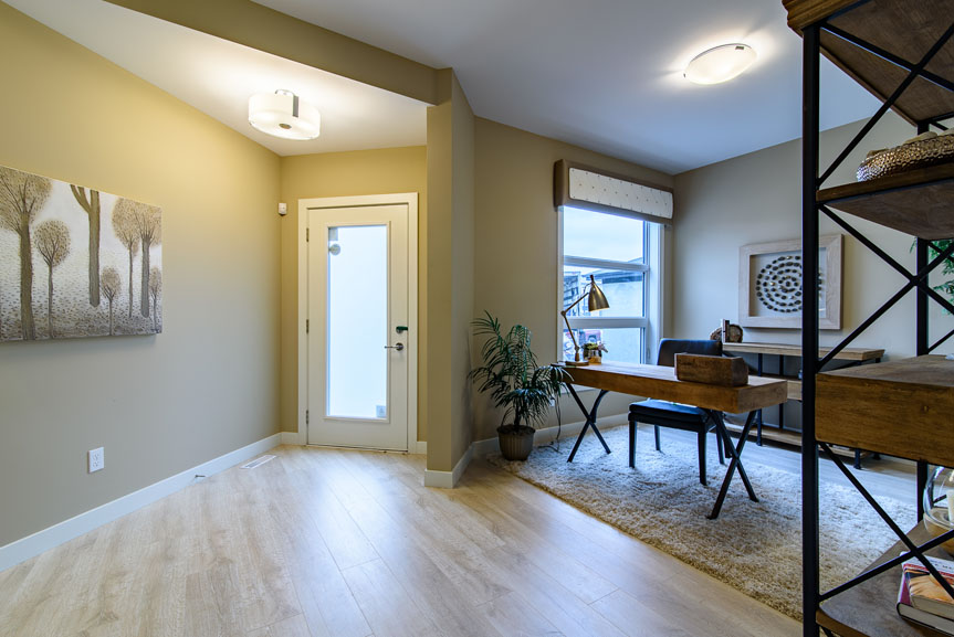 Open concept front entrance and Den with Troly's laminate flooring and wood furniture accents