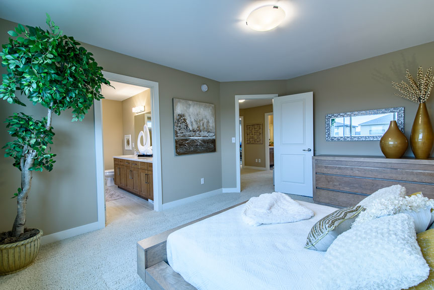 Large Master Bedroom with beige walls, beige carpets and wood accent furniture