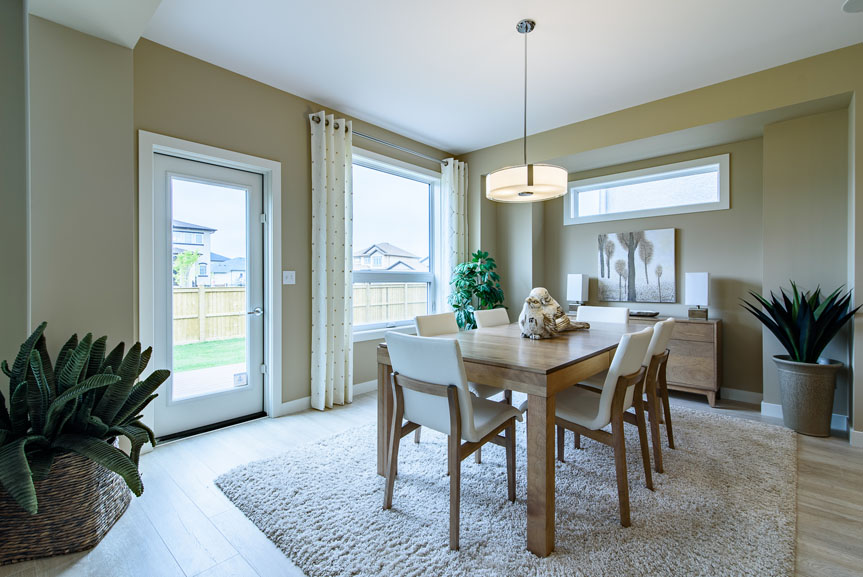 Open concept Eating area with beige walls, Torly's laminate flooring and wood furniture accents