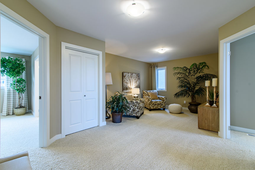 Open concept second floor with beige walls and light carpet