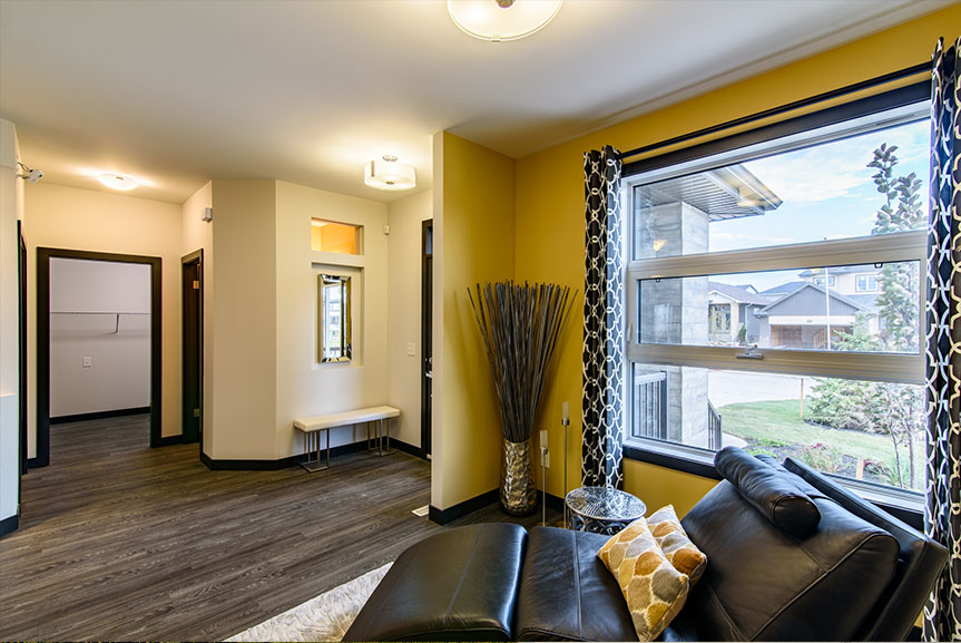 open concept front entrance with vinyl plank flooring and yellow accent wall