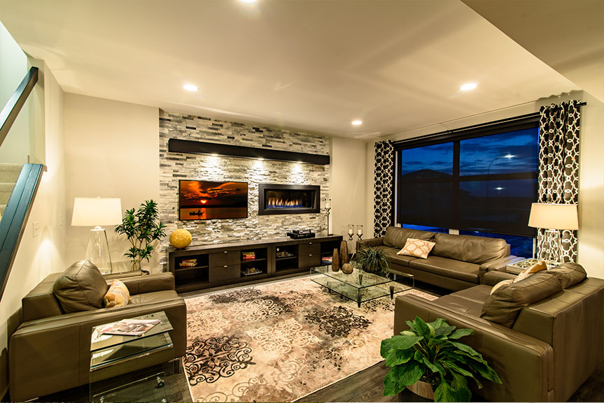 open concept great room with fireplace and entertainment unit complete with cultured stone