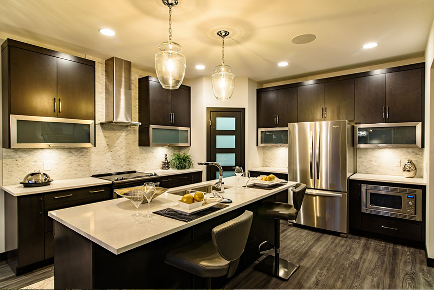 Open concept kitchen with vinyl plank flooring, dark cabinets, light counter tops and stainless steel appliances