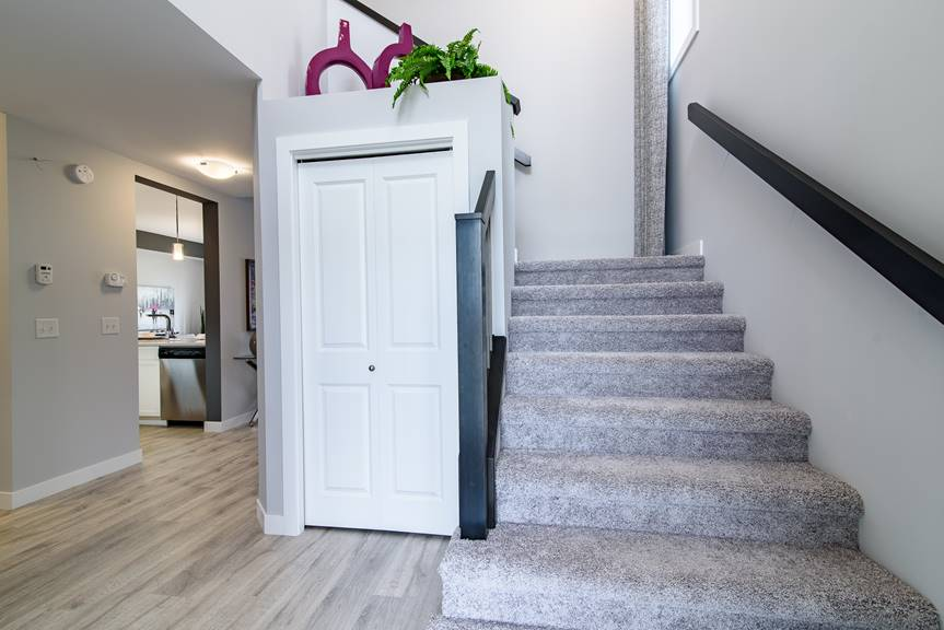 Modern foyer with Torly's Classic Plus Reclaimed Patina Oak laminate flooring, black railing, white MDF baseboards and casing, and grey walls