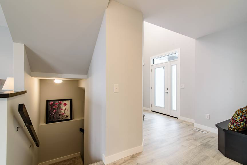 Modern and bright foyer with view of basement stairs, torly's classic plus reclaimed patina oak laminate flooring, light grey walls, dark wood handrails and full lite front door with sidelite and transom