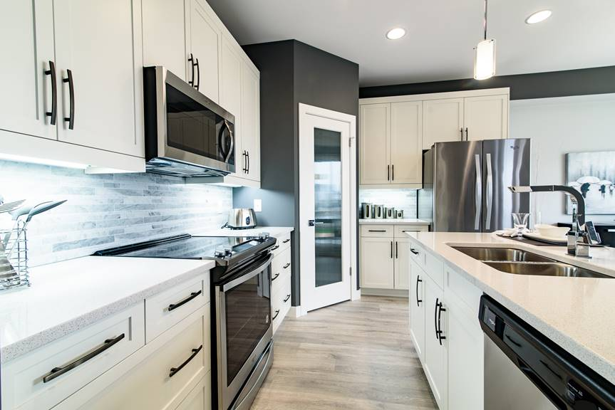 Modern and bright Kitchen with white salem MDF cabinets, island, quartz counter top in Quantra Polar, walk-in pantry, stainless steel appliances, Dulux charcoal slate paint on walls and Torly's classic plus reclaimed patina oak laminate flooring