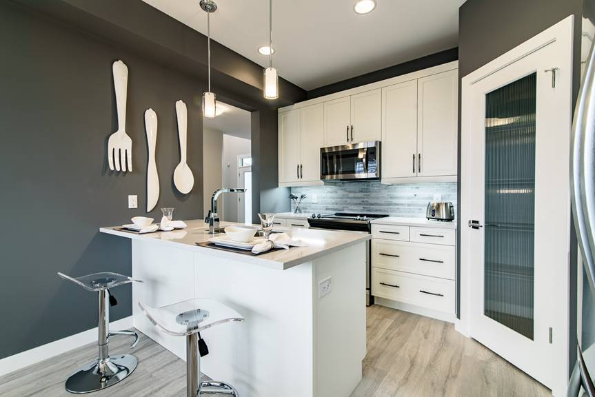 Modern and bright Kitchen with white salem MDF cabinets, island, quartz counter top in Quantra Polar, walk-in pantry, stainless steel appliances and Dulux charcoal slate paint on walls
