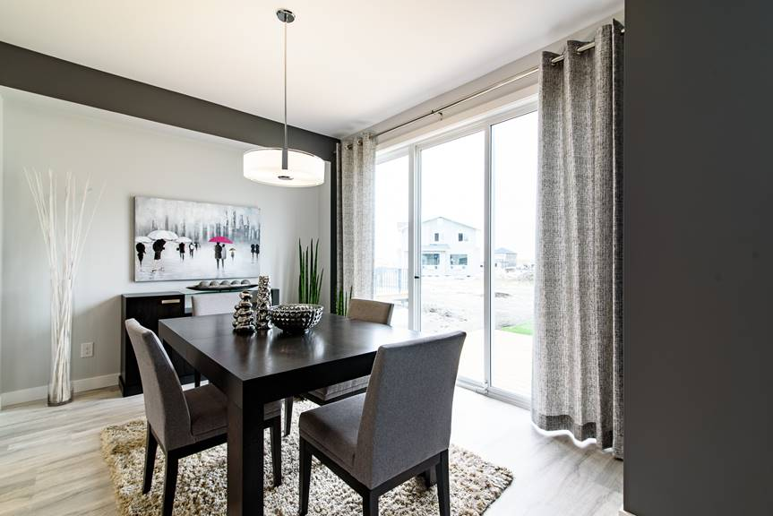 Modern and bright dining room with light grey walls and dark accent paint, Torly's classic plus reclaimed patina oak laminate flooring and dark furniture