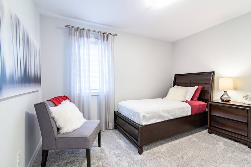 Modern and spacious Bedroom with dark furniture, red accents, grey walls and Villanow Twist carpeting