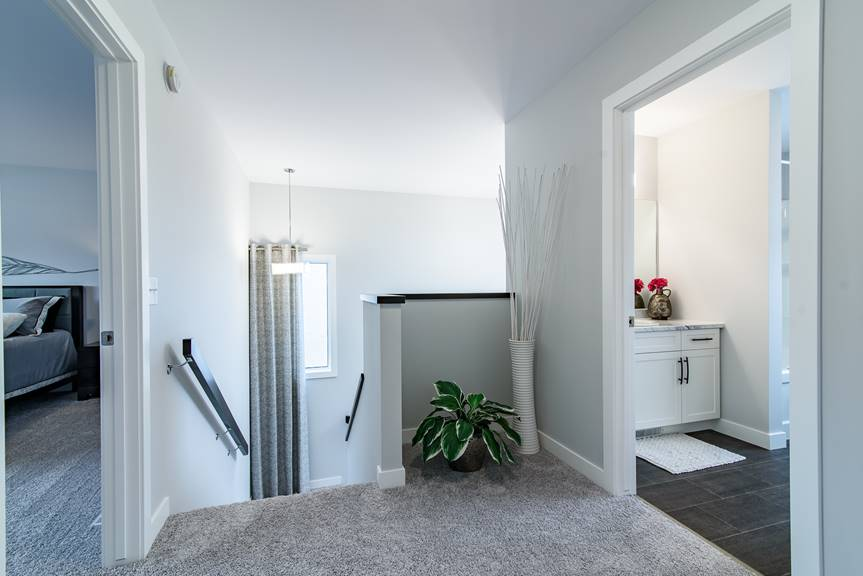 Modern home, upper hallways with grey walls, grey carpet, black handrail, MDF white casing and baseboards, with a view of upper main bathroom and master bedroom