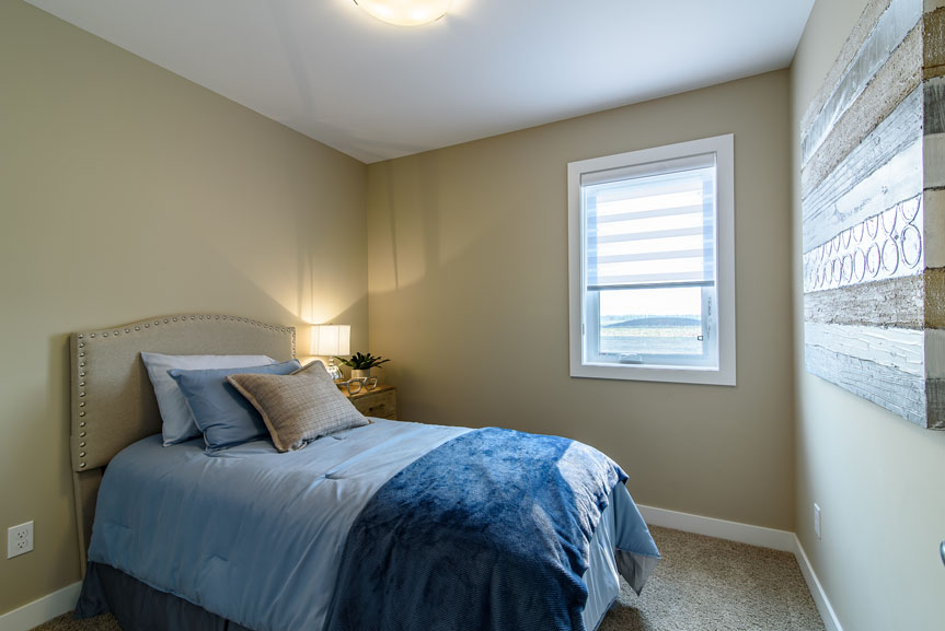 Spacious Bedroom with beige walls, Siesta Twist Pueblo carpet, white mdf baseboards and casing and blue accents