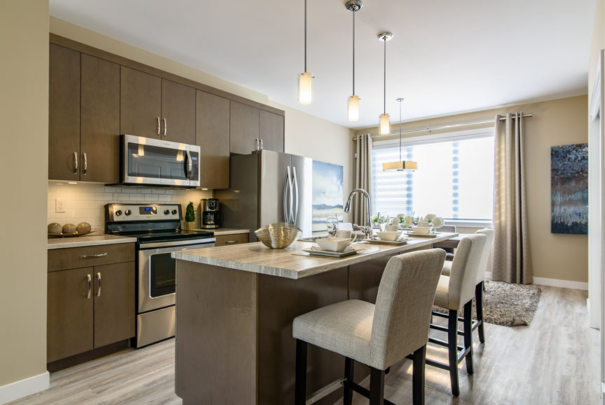 Modern Kitchen with Lockhart Winter Maple cabinets, stainless steel appliances, ceramic tile back splash, hanging pendant lights, Arborite Roman Travertine laminate counter top and island with eating lip
