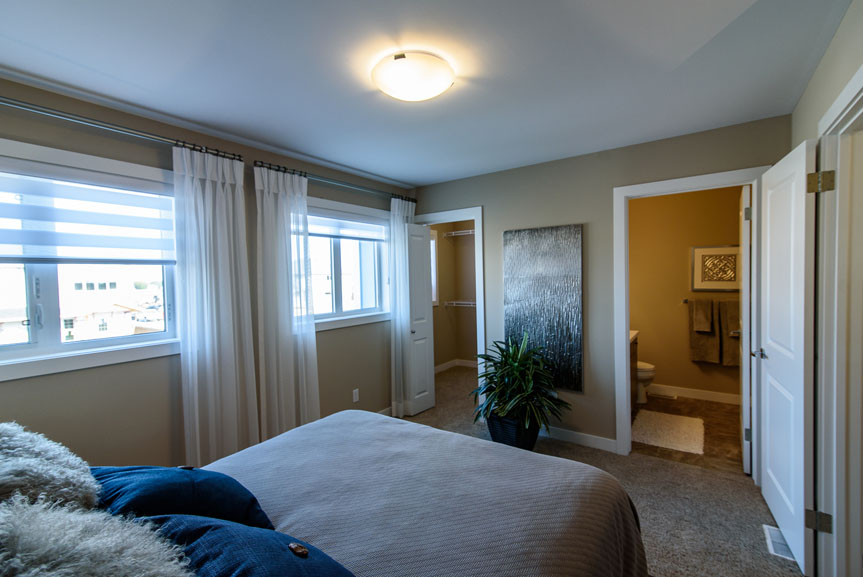 Beige Master Bedroom with Siesta Twist Pueblo carpet, white MDF baseboards and casing, large windows and blue accents