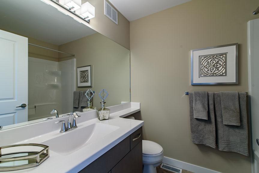 Modern Main Bathroom with vinyl flooring, white cultured marble vanity tops, dark wood cabinets and beige walls