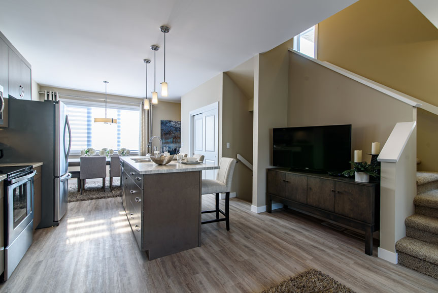 Modern Great room and Kitchen with Flexi Plank Pewter Moon flooring, Dulux Beachcomber paint on walls, Lockhart Winter Maple cabinets in Kitchen with stainless steel appliances, kitchen island and hanging pendant lights