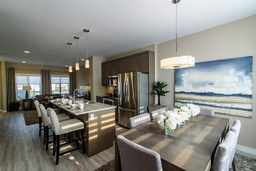 Modern Eating area and Kitchen with Lockhart Winter Maple cabinets, stainless steel appliances, ceramic tile back splash, hanging pendant lights, Arborite Roman Travertine laminate counter top and island with eating lip