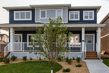 Front exterior of Duplex with dark blue acrylic textured stucco, grey smart start panel detail and wood front porch