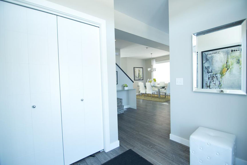 Open Concept Front Entrance with Grey Vinyl Plank Flooring and Light Walls