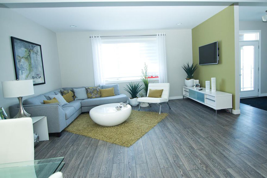 Open Concept Great Room with Grey Vinyl Plank Flooring, Light Walls and Green Accents