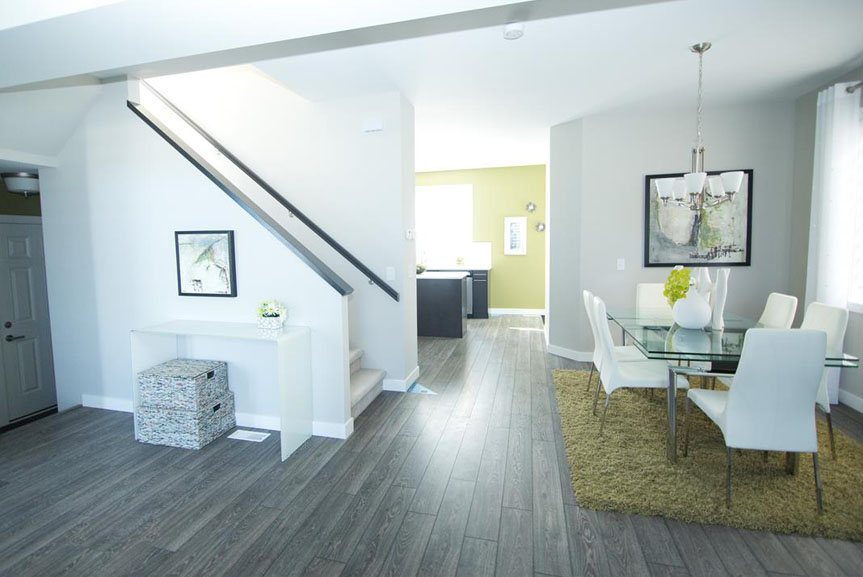 Open Concept Main Floor with Light Walls, Grey Vinyl Plank Flooring and Green Accents