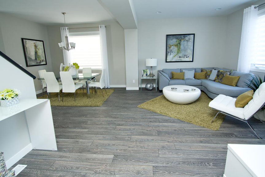 Open Concept Great Room and Eating Area with Light Walls, Grey Vinyl Plank Flooring and Green Accents