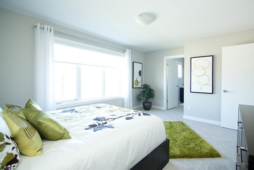 Large Master Bedroom with Light Walls and Green Accents
