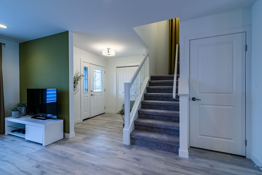 Open concept front entrance and great room with green accent wall and laminate flooring