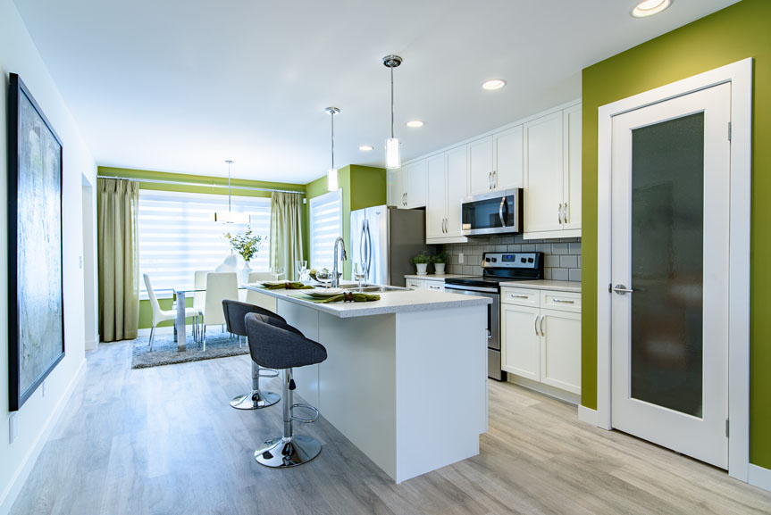 open concept contemporary kitchen and eating area with Salem MDF Alabaster cabinets, laminate flooring and green accent walls