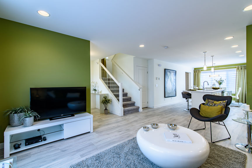 open concept great room with laminate flooring, white furniture and green accent wall