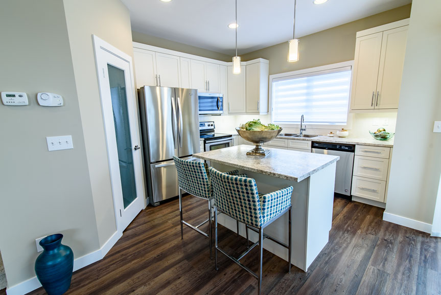Modern Kitchen featuring New Market Breckenridge vinyl plank flooring, White Salem MDF cabinets with profiled drawer fronts in Alabaster, large island with eating lip, stainless steel appliances, laminate counter tops, ceramic tile back splash