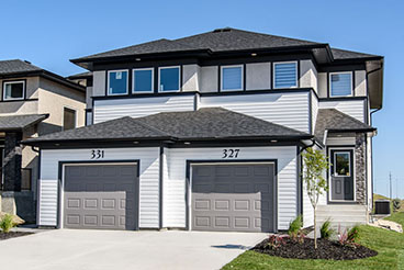 Modern home exterior featuring grey vinyl siding, cultured stone pillars, black smart start trim detail and dark grey garage and front entrance doors