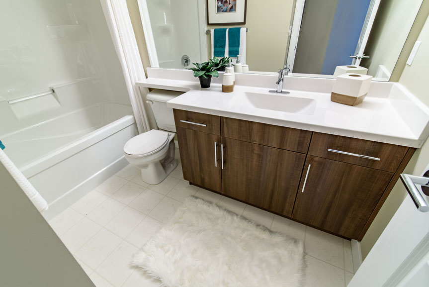 Modern Contemporary Main Bathroom with vinyl tile flooring, cultured marble vanity top with drop-in sink and warm walnut soho cabinets