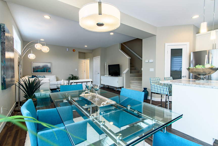 Modern Dining room featuring New Market Breckenridge vinyl plank flooring, modern hanging light fixture and teal accents