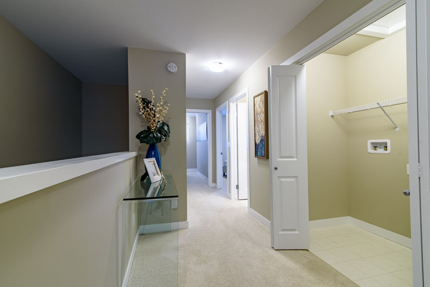 Bright hallway with access to second floor laundry which features vinyl flooring and wire shelving