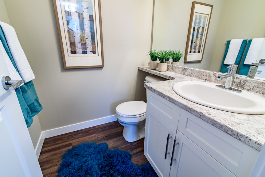 Modern Powder room with New Market Breckenridge vinyl plank flooring, Cultured Marble counter tops, a drop-in Serif sink and White Salem MDF cabinets with profiled drawer fronts