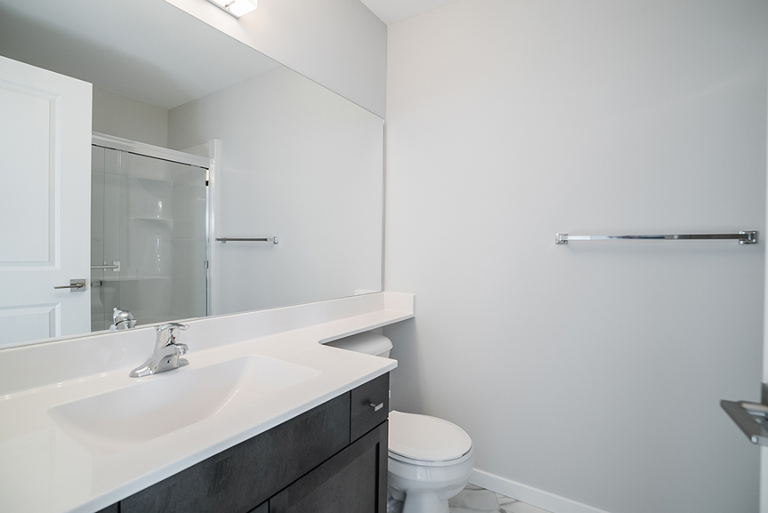 14. Ensuite with dark wood vanity, white cultured marble vanity tops, light grey painted walls and large mirror - 159 Atlas Crescent The Highview DG 43 A Broadview Homes
